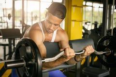 在健身房的人锻炼 人在健身房的推力重量 库存图片