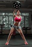 在健身房的健身妇女摇摆的水壶响铃 免版税库存照片
