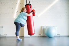 在健身房的哀伤的肥胖妇女训练 库存图片