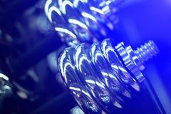 在健身房的哑铃在蓝色光 发光的金属哑铃或杠铃重量 免版税库存照片