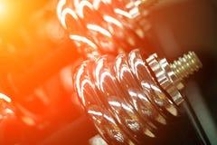 在健身房的哑铃在黄灯 现代金属哑铃或杠铃重量 免版税库存图片