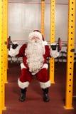 在健身房的圣诞老人举的重量 免版税库存图片