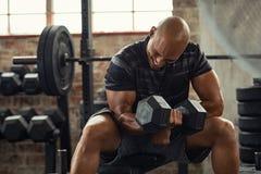 在健身房的坚强男人举的重量 图库摄影