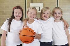 在健身房的女性学校体育队与篮球 免版税库存照片