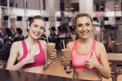 在健身房的妇女和女孩饮用的蛋白质震动 他们看起来愉快,时兴和适合 免版税图库摄影