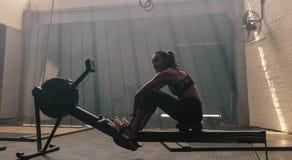 在健身房的妇女坐的划船器 库存图片
