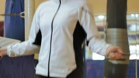 在健身房的妇女训练,与一条绳索的工作,在一个健康身体健身kickboxer系列之外 股票录像