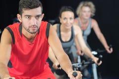 在健身房的小组在固定式自行车 免版税库存照片