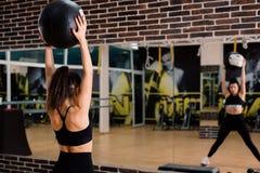 在健身房的年轻女人举的fitballs在镜子前面 免版税库存图片
