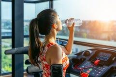 在健身房的年轻女人饮用水 锻炼概念 免版税库存照片