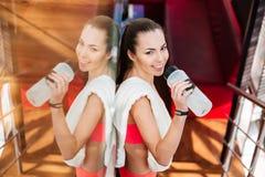 在健身房的微笑的可爱的女子运动员饮用水 库存图片