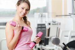 在健身房的微笑的少妇举重 免版税图库摄影