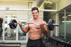 在健身房的微笑的赤裸上身的肌肉人举的杠铃 免版税库存照片