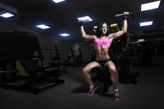 在健身房的性感的运动员妇女推力 免版税库存图片