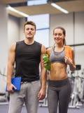 在健身房的愉快的夫妇与水和片剂个人计算机 免版税图库摄影