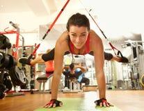 在健身房的愉快的妇女训练 免版税库存图片