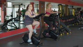 在健身房的懒惰,超重女性吃小圆面包,当骑固定式自行车时 影视素材