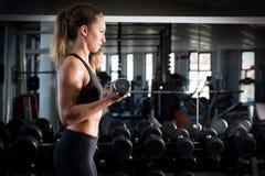 在健身房的有吸引力的女子举重 免版税图库摄影