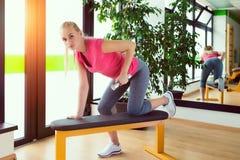 在健身房的有吸引力的少妇训练与哑铃 库存图片
