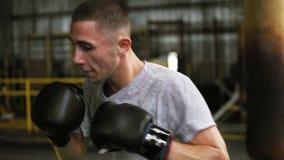在健身房的活跃,恼怒的男性拳击手训练过程 人拳击的画象使用沙袋的,实践踢在 股票录像