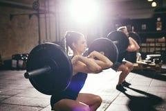 在健身房的男人和妇女举的杠铃 图库摄影
