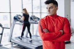 在健身房的男朋友教练在人背景踏车的 免版税库存照片