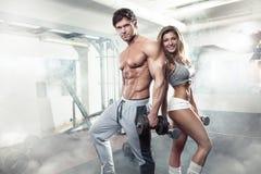 在健身房的美好的年轻运动的性感的夫妇锻炼 免版税库存图片
