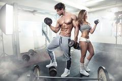 在健身房的美好的年轻运动的性感的夫妇锻炼