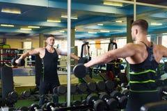 在健身房的肌肉人训练 年轻人在镜子附近拾起哑铃 库存照片