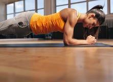 在健身房的肌肉女性做的核心锻炼 库存照片