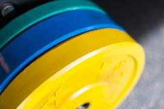 在健身房的色的大量的哑铃重量 免版税库存图片
