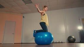 在健身房的训练期间年轻运动的妇女在Fitball平衡 影视素材