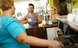 在健身房的超重女服务员服务咖啡 免版税库存照片