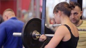 在健身房的蹲坐 Paurlifting 增强 与重量的蹲坐 在健身房的妇女火车 与重的训练 股票视频
