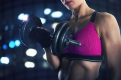 在健身房的运动妇女训练二头肌 库存图片