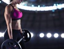 在健身房的运动妇女训练二头肌 免版税库存图片