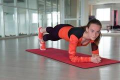 在健身房的迷人的女运动员火车 图库摄影