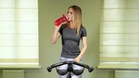 在健身房的适合的少妇饮用水 休假的肌肉妇女在锻炼以后 影视素材