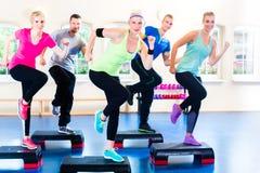 在健身房的重量训练与步进 免版税库存图片