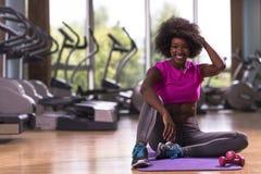 在健身房的非裔美国人的妇女锻炼瑜伽 库存照片