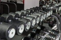 在健身房的黑和钢哑铃:重量健身设备 库存照片