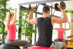 在健身房的年轻夫妇训练与在镜子前面的哑铃 库存图片