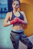 在健身房的年轻女性拳击手锻炼 性感的体育穿戴的健身白肤金发的女孩与在拳击健身房摆在的完善的身体 免版税库存照片