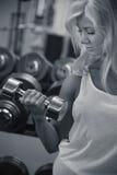 在健身房的年轻女性训练二头肌 库存照片