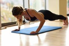 在健身房的年轻美好的妇女doin俯卧撑 库存照片