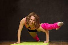 在健身房的年轻运动女孩火车 免版税库存照片