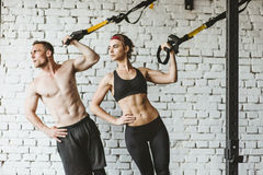 在健身房的年轻运动的夫妇锻炼 免版税库存照片