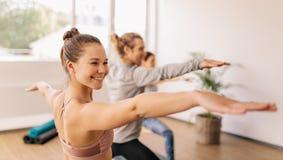 在健身房类的女子实践的瑜伽 免版税图库摄影