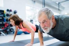 在健身房解决的资深夫妇,做俯卧撑 图库摄影