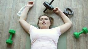 在健身房锻炼的地板上用尽的肥胖妇女说谎 股票录像